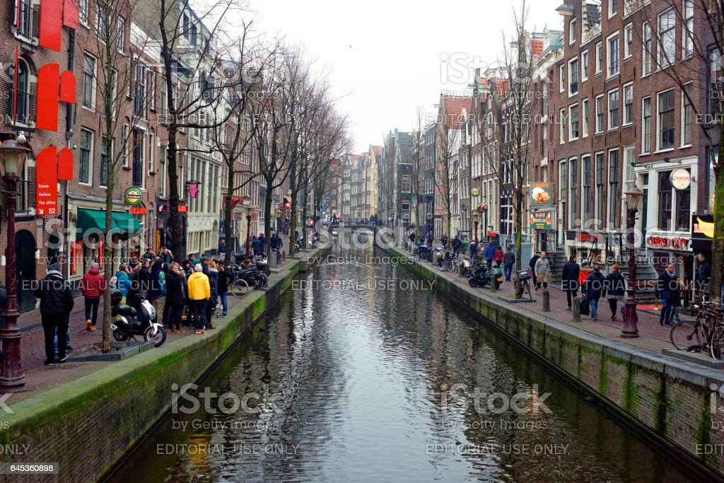 Along the canal walk citizens and moving vehicles stock photo