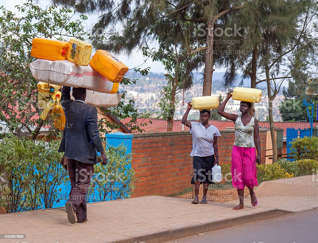Along the road in Rwanda: pedestrians with head loads stock photo