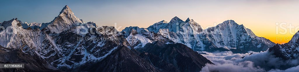 Alpenglow on dramatic mountain peaks panorama Ama Dablam Himalayas Nepal stock photo