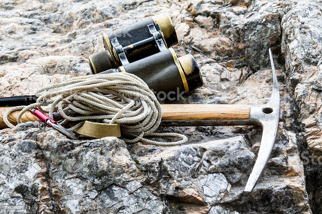 Alpenstock with binoculars and with rope on rock stock photo