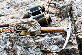 Alpenstock with binoculars and with rope on rock