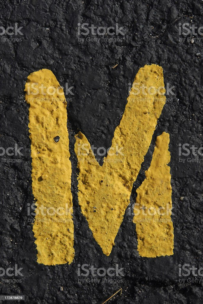 Alphabet, Asphalt Stenciled M royalty-free stock photo