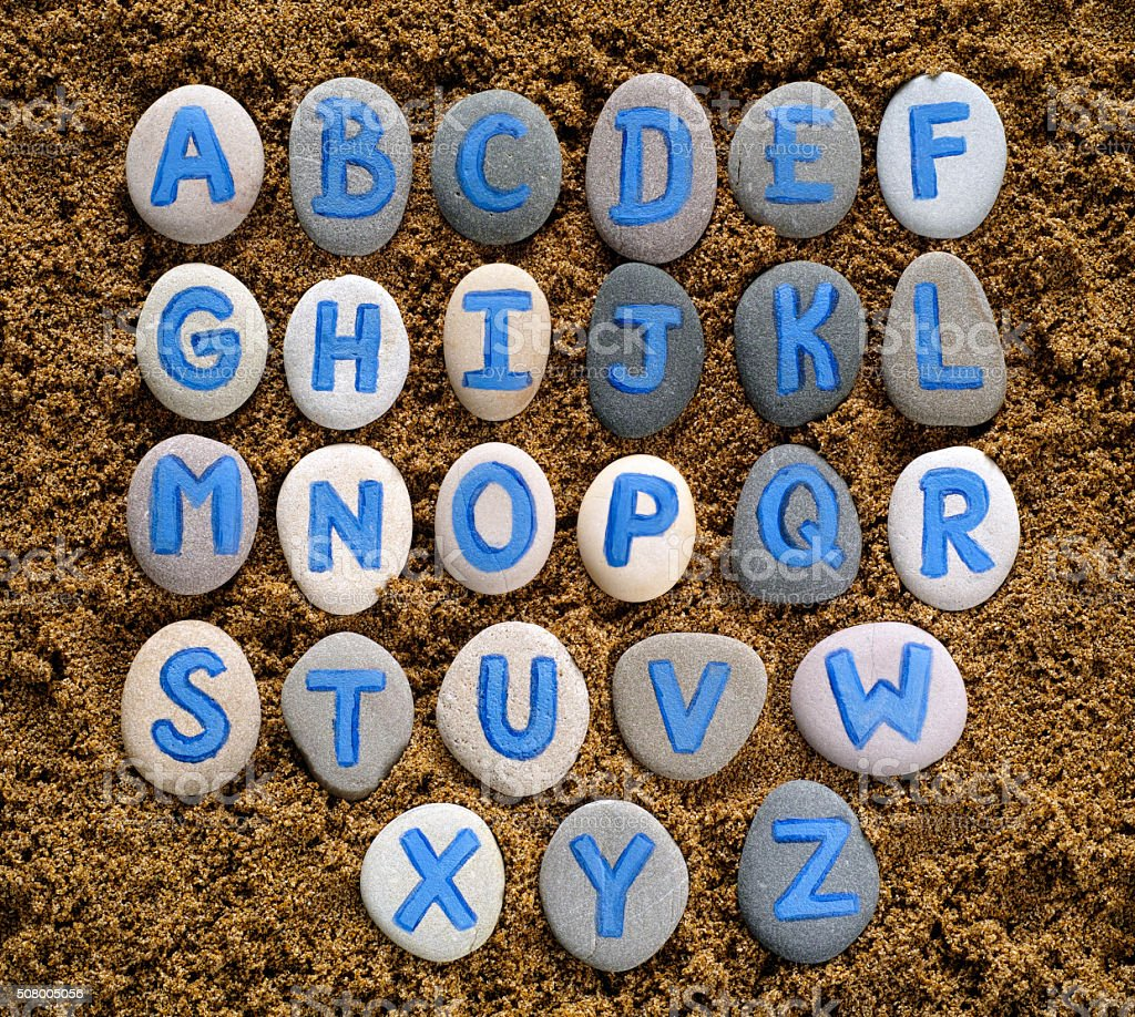 Alphabet letters drawn on stones stock photo