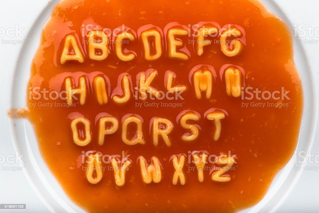 Alphabet letters made from spaghetti in sauce stock photo