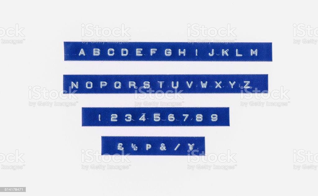 Alphabet letters on retro plastic tape strip stock photo