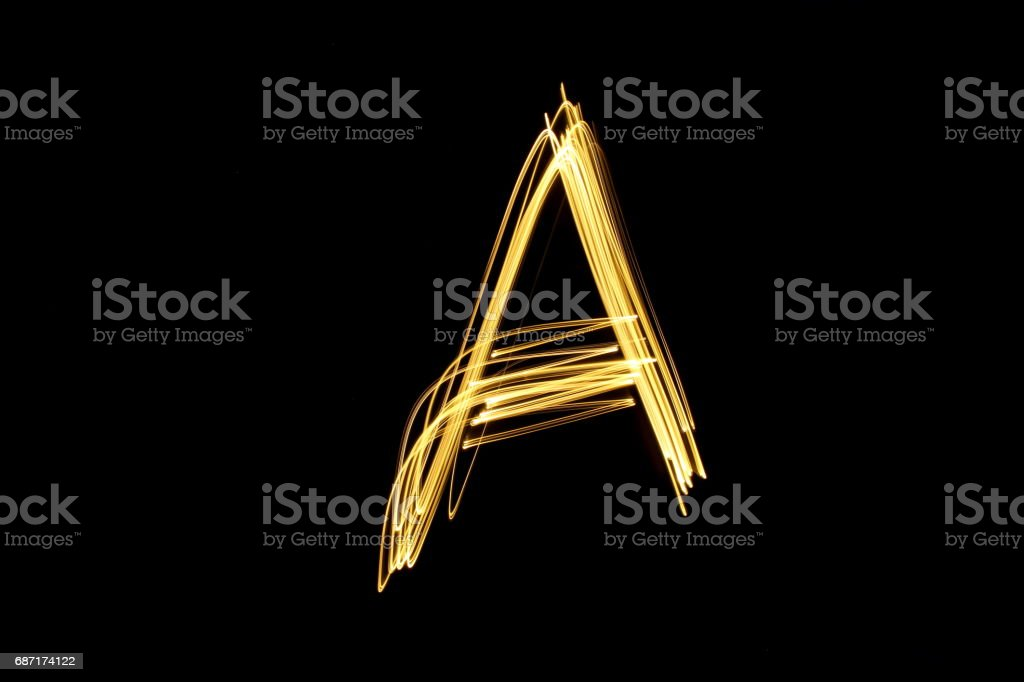 Alphabet Series - Capital Letter A - Gold Light Painting Photography against a black background stock photo
