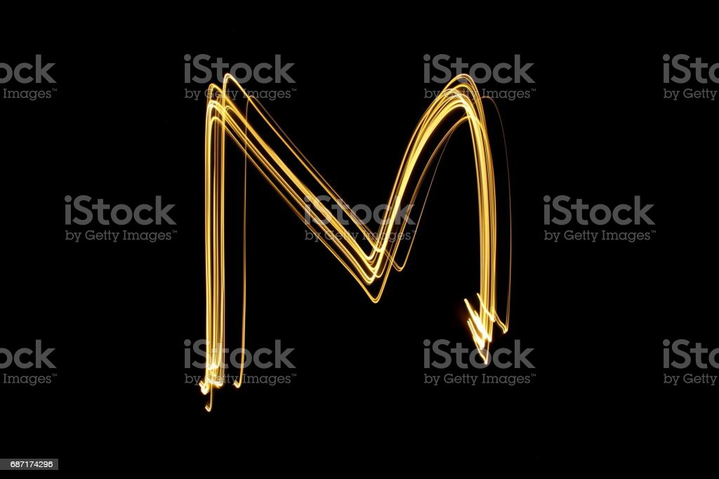 Alphabet Series - Capital Letter M - Gold Light Painting Photography against a black background stock photo
