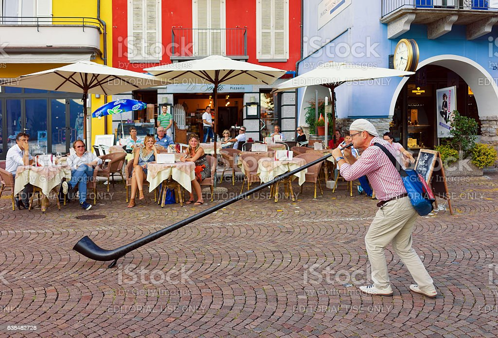 Alphorn player entertaining people at restaurant in Ascona stock photo