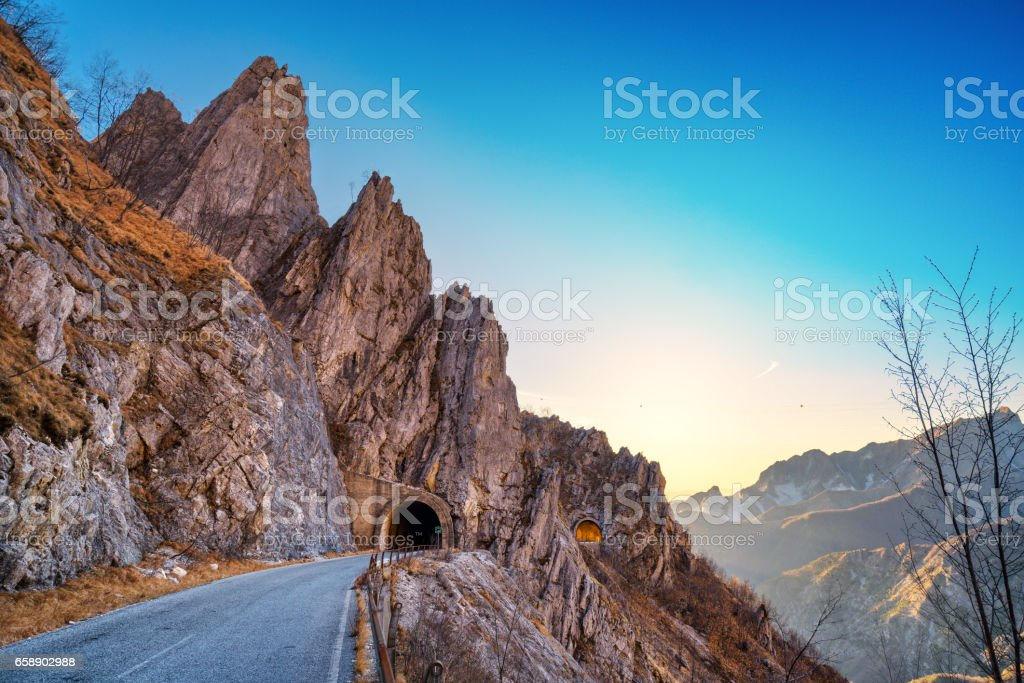 Alpi Apuane mountain road pass and double tunnel view at sunset. Carrara, Tuscany, Italy. stock photo