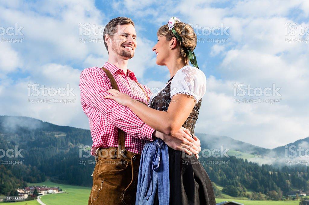 Alpine cattle farmers on mountain meadow stock photo