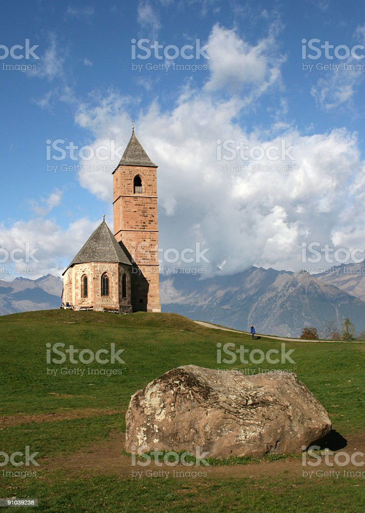 Alpine church with mountain range in the background stock photo