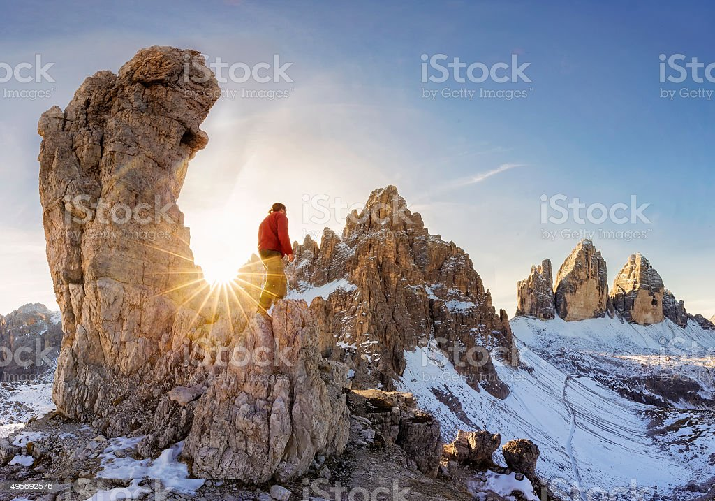 Alpine climber lok at sunrise to Three pinnacles stock photo