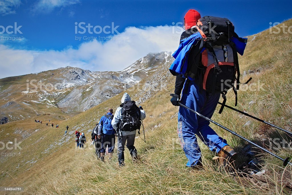 Alpine expedition walking in single file towards the peak royalty-free stock photo