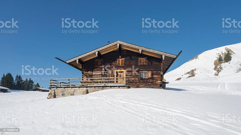 Alpine hut at Schönfeldalm alp in spring covered in snow stock photo