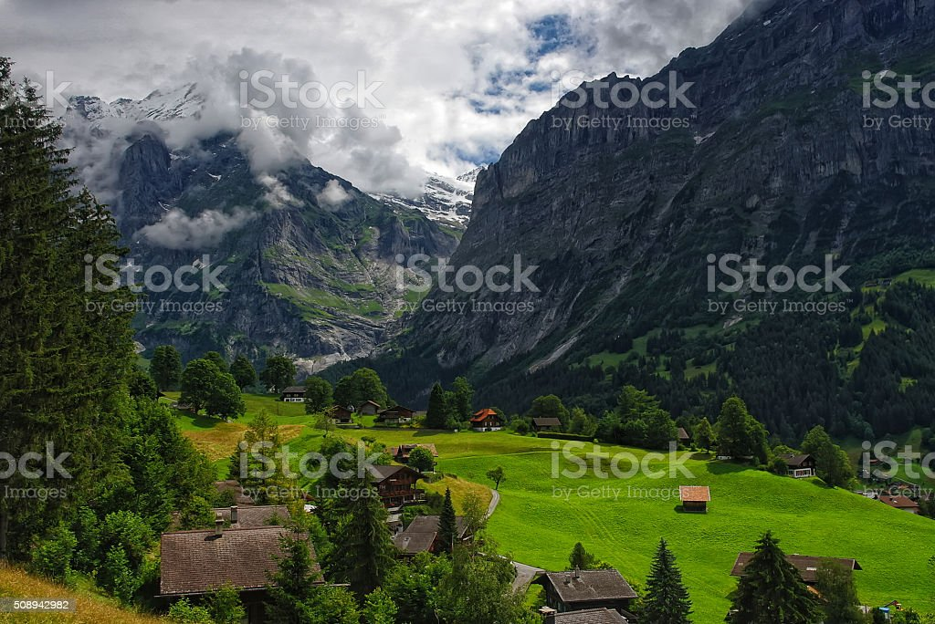 Alpine landscape with mountains covered by clouds in Grindelwald, Switzerland stock photo