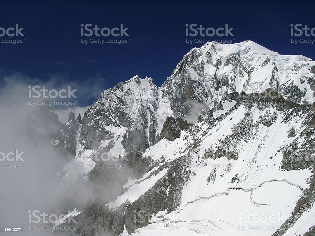 Alpine mountain peaks with snow in the clouds royalty-free stock photo