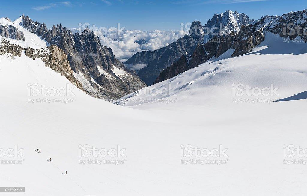 Alpine mountaineers crossing white glacier between rocky peaks stock photo