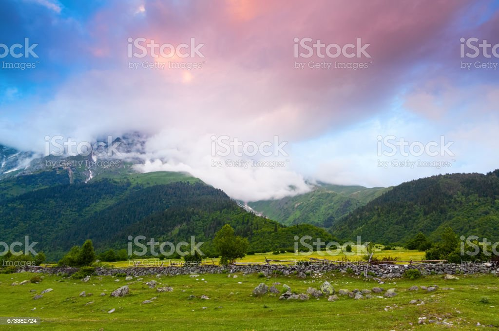 Alpine scenery with big mountains covered with glaciers and green lawns with different flowers, trails and sky on a summer day. Upper Svaneti, Georgia, Europe. stock photo