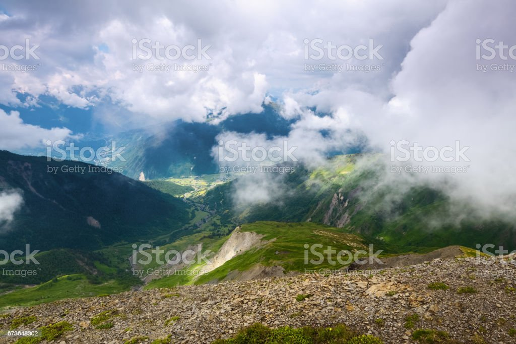 Alpine scenery with big mountains covered with glaciers, fog  and green lawns with different flowers, trails and sky on a summer day. Upper Svaneti, Georgia, Europe. stock photo