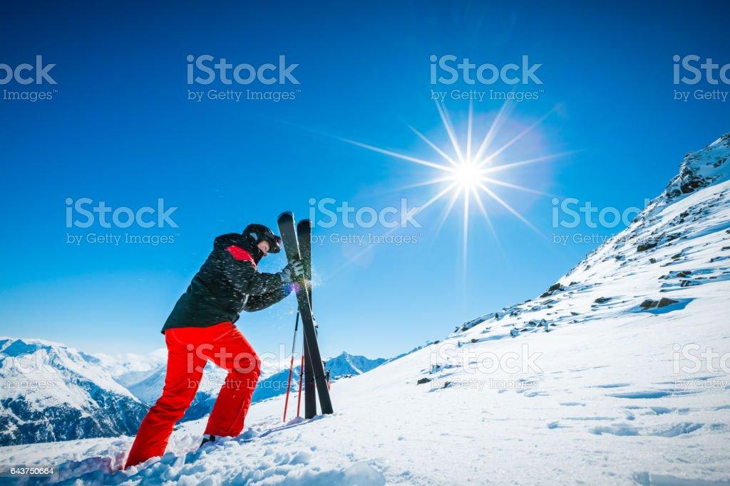 Alpine skier taking skis to ski down the slope stock photo