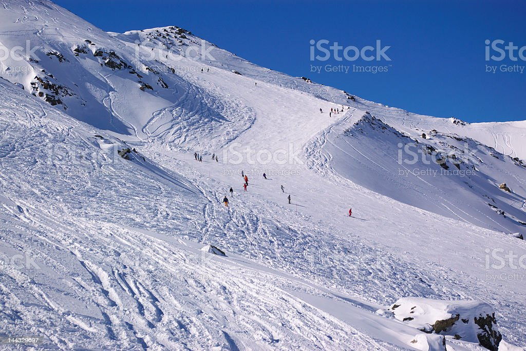 long curvy alpine skiing downhill slope in winter mountains with few...