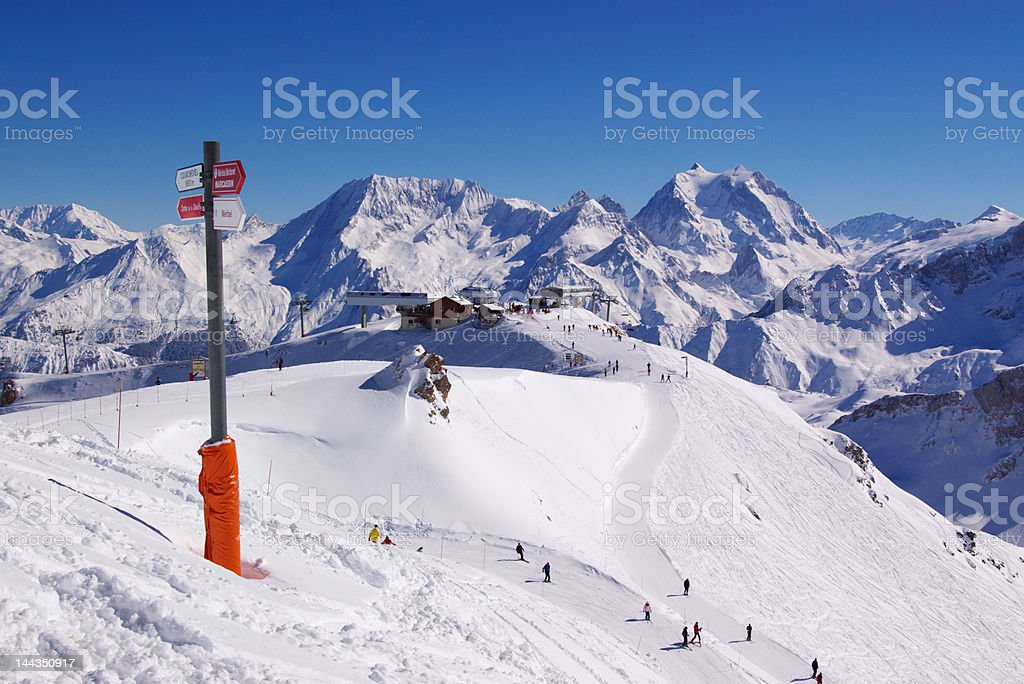 view on snowy high mountain chain with ski lift on the top and many...
