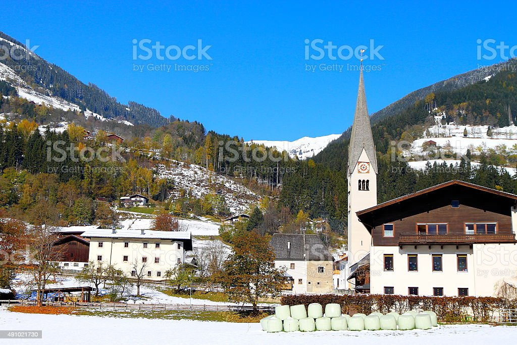 Alpine village, catholic gothic church, swiss chalets, snow, autumn woods stock photo