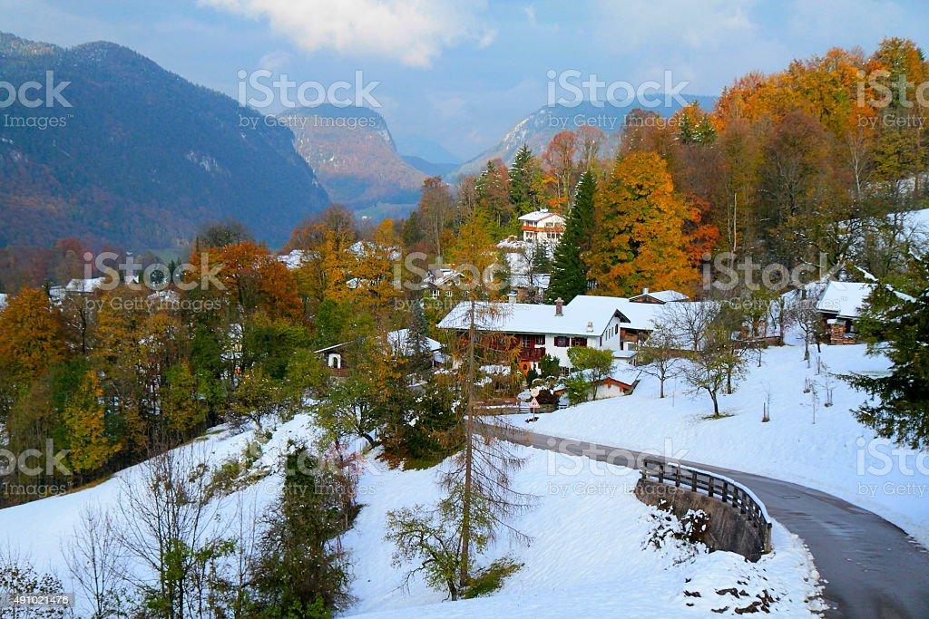 Alpine village, swiss chalets, snow, dramatic colorful autumn stock photo