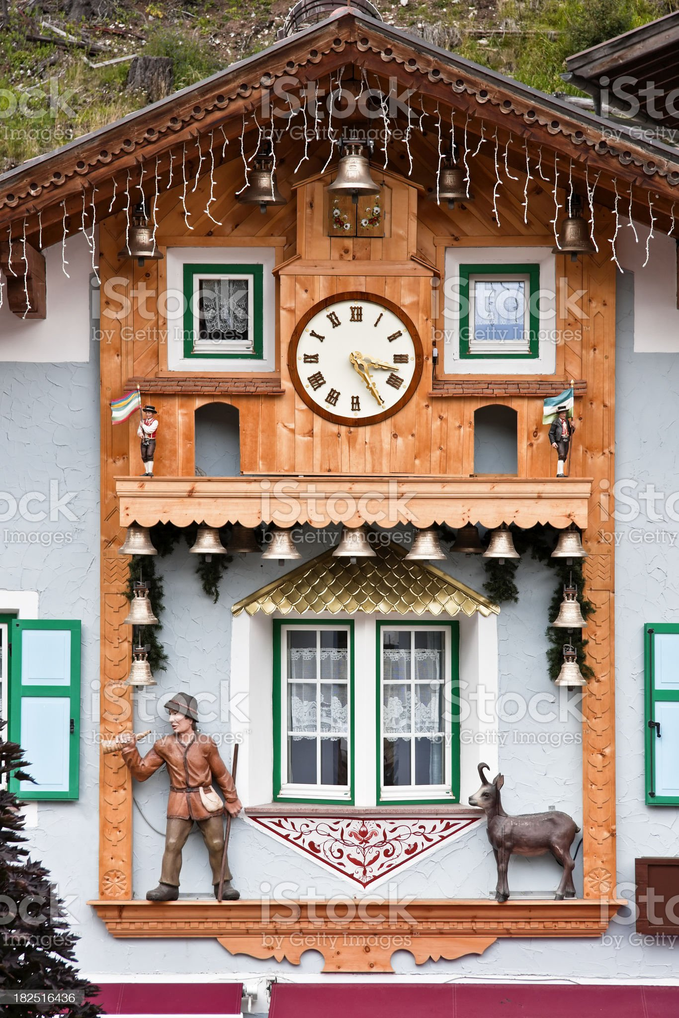 Alpine Wooden Facade with Clock and Bells, Dolomites in Summer royalty-free stock photo