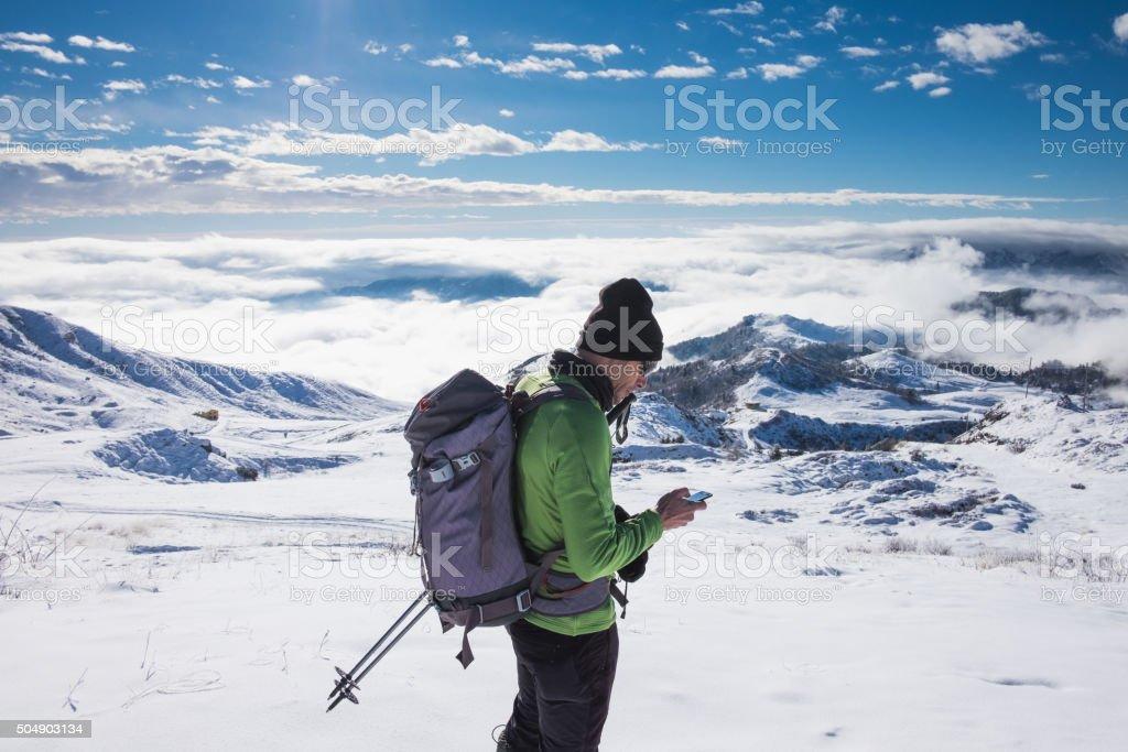 Alpinist checks phone on top of snowy mountain stock photo