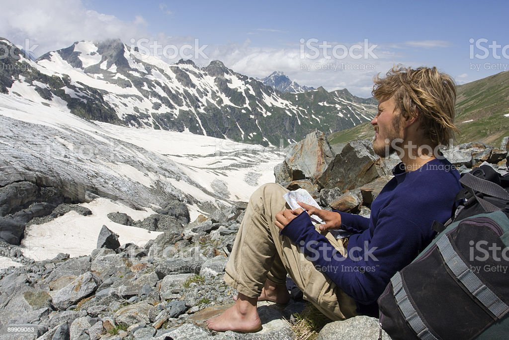 alpinist looking to map in wild mountains royalty-free stock photo