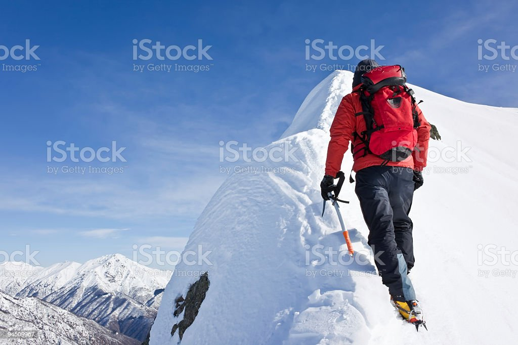 Alpinist man in red scaling up the snowy white mountains stock photo