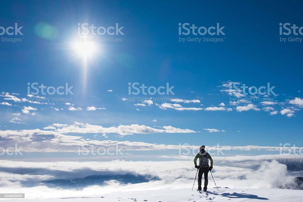 Alpinist on top of snowy mountain stock photo