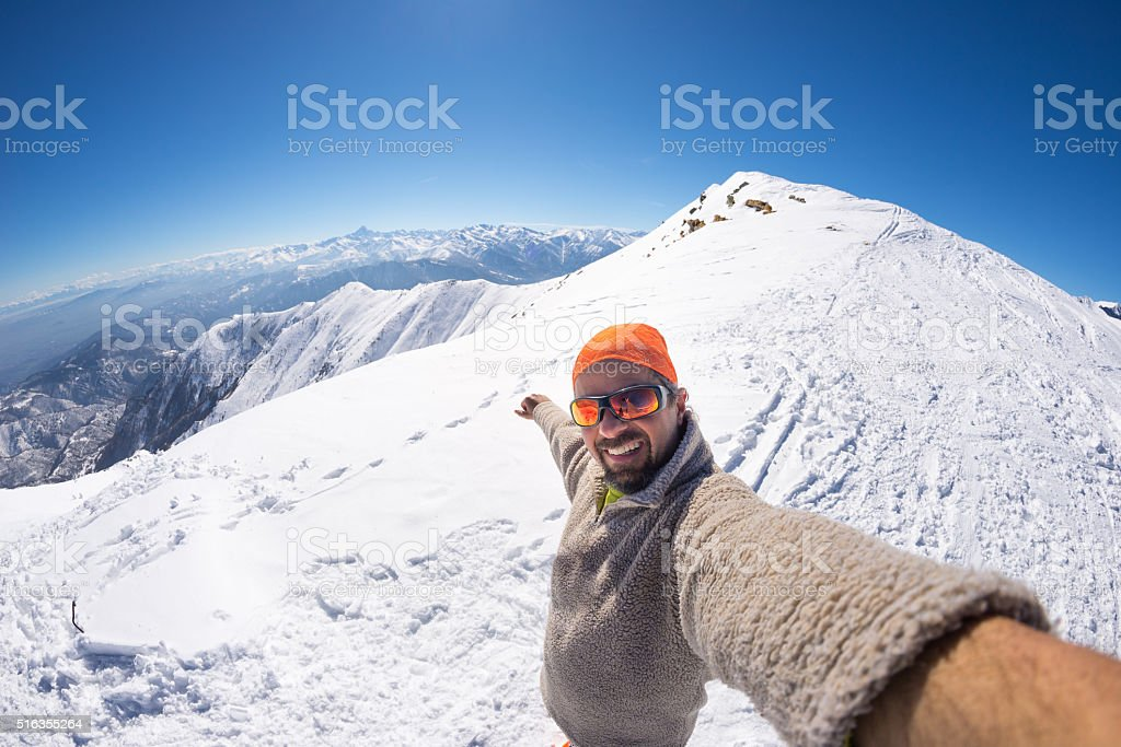 Alpinist taking selfie on snowcapped mountain, fisheye lens stock photo