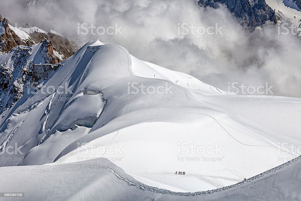 Alpinists at a snow field stock photo