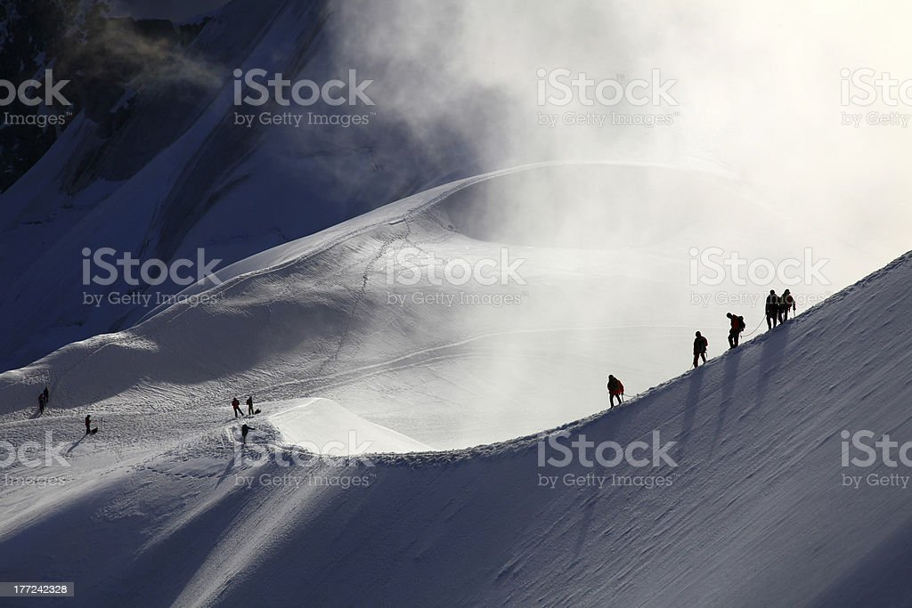 Alpinists making their way through snow drifts in mountains stock photo