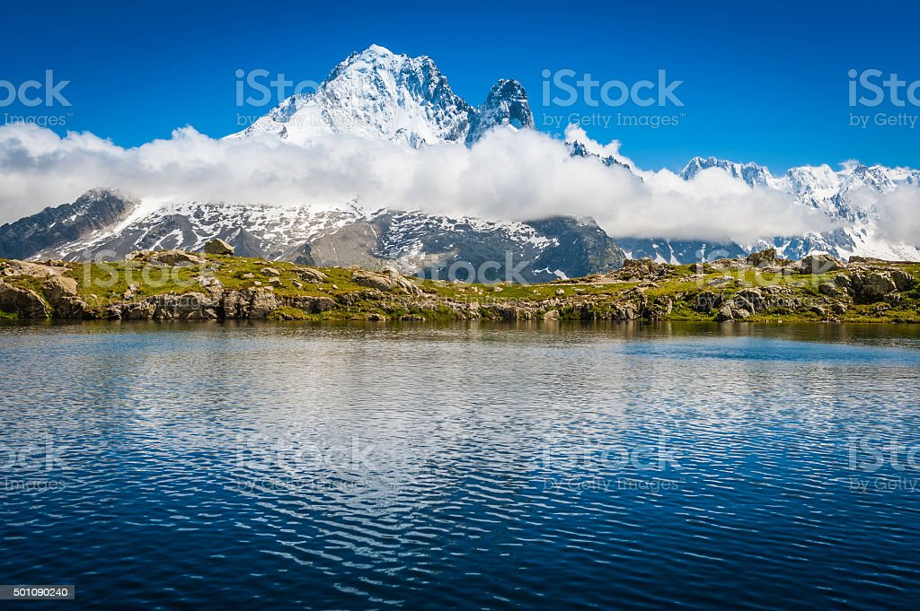 Alps Aiguille Verte Les Drus reflecting in mountain lake Chamonix stock photo