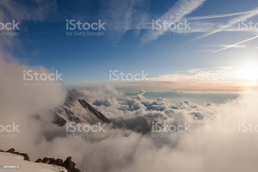 Alps in the clouds during sunset stock photo
