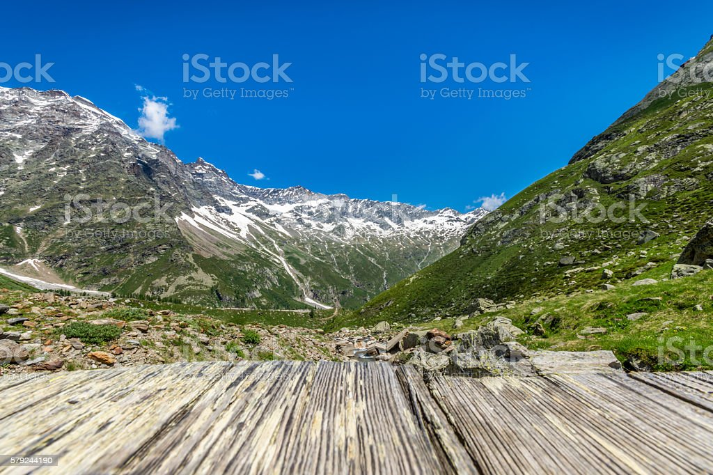 Alps mountains from an old wood bridge stock photo