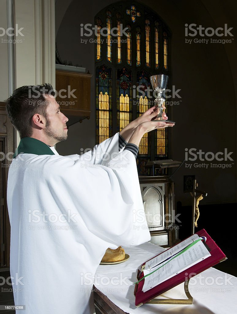Altar Scene with Priest Blessing Wine stock photo