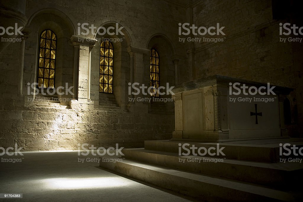 Altar with tinted window in background and sunbeam on wall royalty-free stock photo