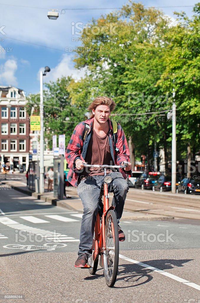 Alternative blond guy on an orange bike in Amsterdam stock photo