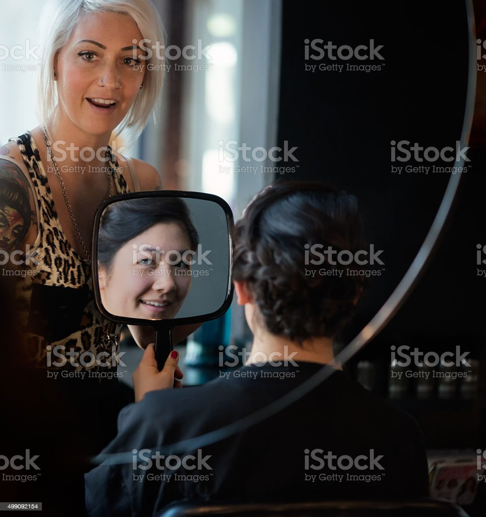 Alternative Hair Stylist and Young Asian Woman Looking in Mirrors stock photo