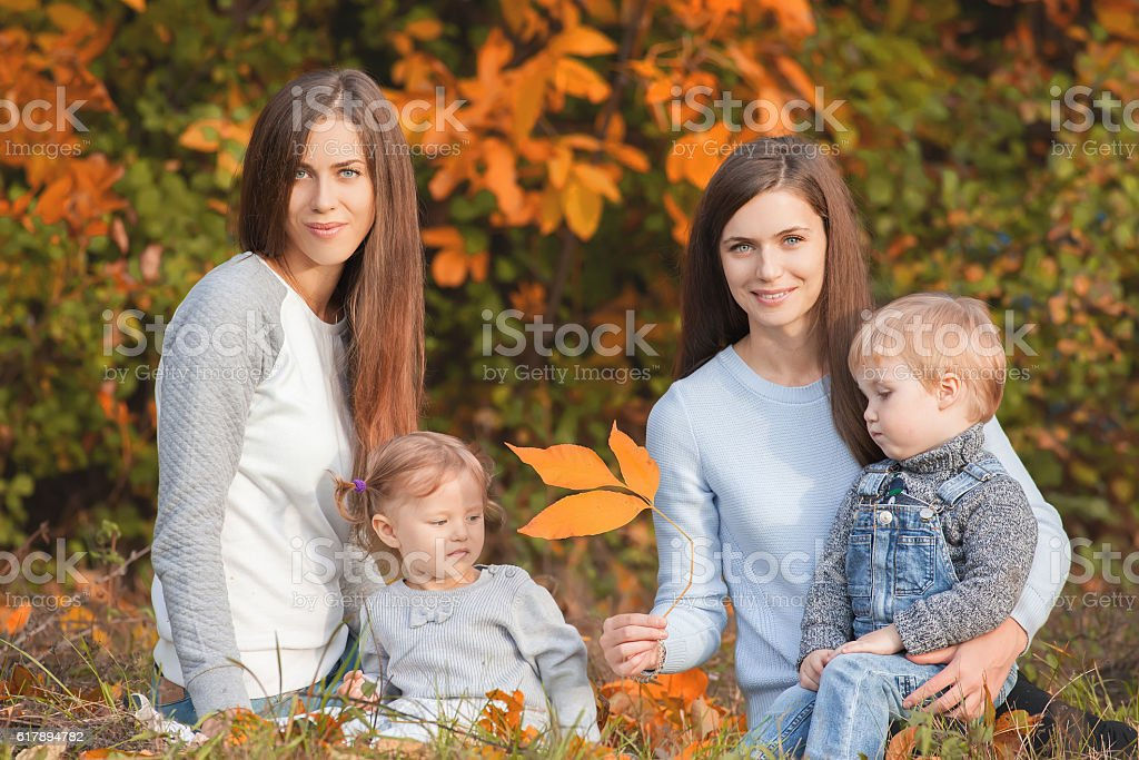 Alternative lesbian family with mothers, daughter and boy outdoo stock photo