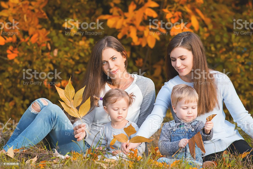 Alternative lesbian family with mothers, daughter and boy outdoor stock photo