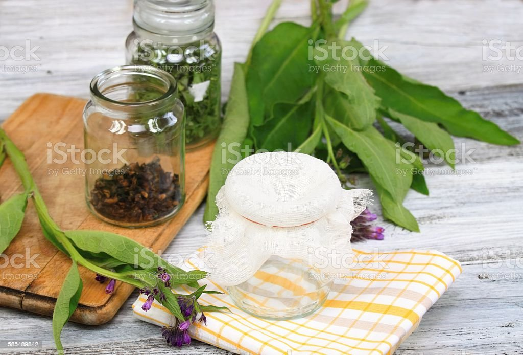 Alternative medicine, preparing for filtering Comfrey ointment stock photo