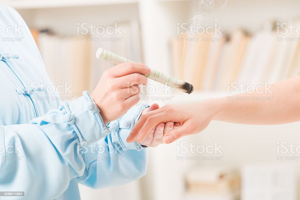 Alternative medicine therapist doing moxa treatment stock photo