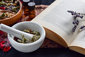 alternative medicine with essential oils,book, and dried herbs