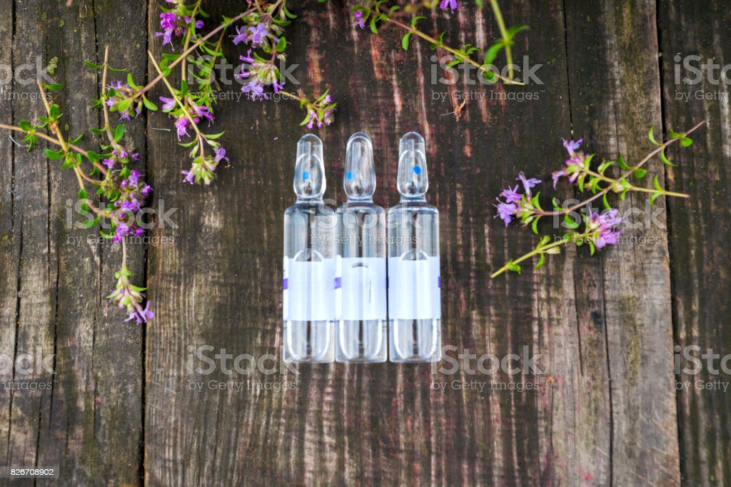 Alternative Medicine.Thyme and medical ampoules. Essential oils stock photo