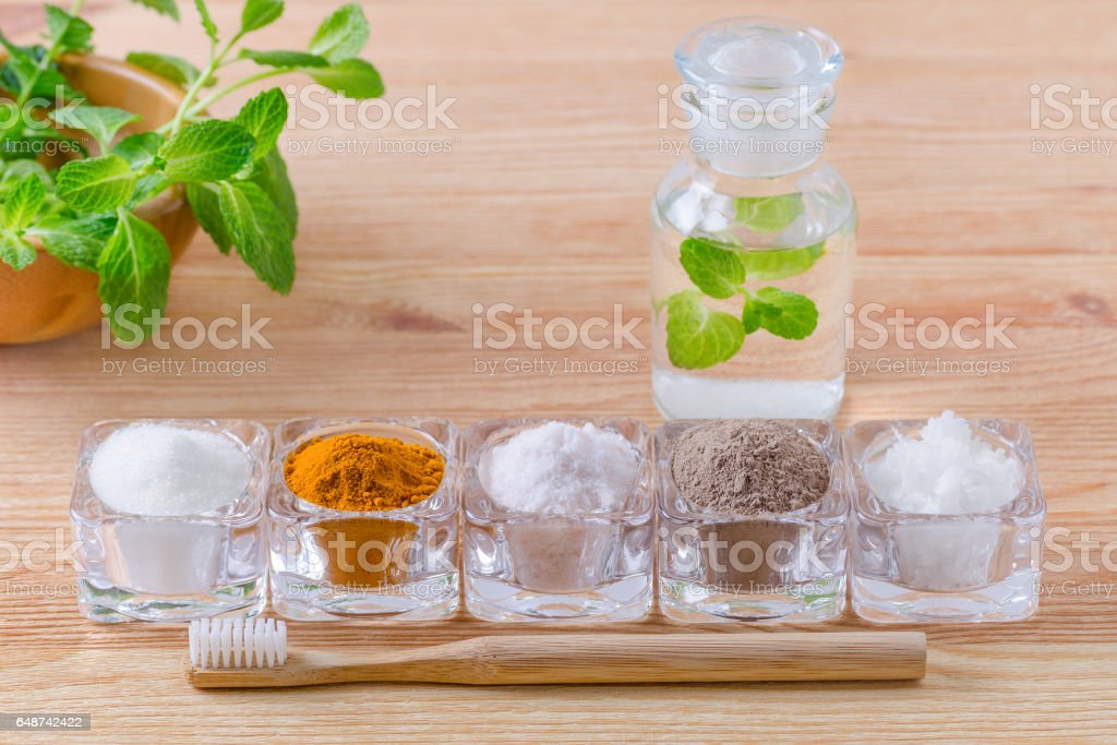 alternative natural mouthwash with mint, toothpaste xylitol or soda, turmeric - curcuma, himalayan salt, clay or ash, coconut oil and wood toothbrush, on wooden stock photo